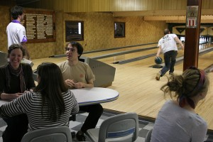 Hannah Yourd '09, Neil Finnegan '09 and Laura Simpson '09 shoot the breeze before they bowl next as Kennon Landis '09 throws a ball down down the lane. - Paul Kramer