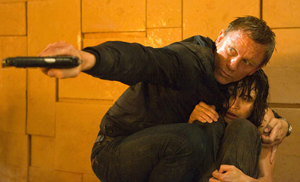 Bond (Daniel Craig) shields Camille (Olga Kurylenko) and fires at a fuel cell as flames engulf Medrano's suite at Perla De Las Dunas.
