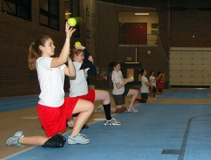 Amanda Stromquist '12, Kelsey Montgomery '11 and other members of the Softball team warm up their arms before practice on Thursday evening. The team is currently practicing in the PEC before their outdoor season starts up. - Sophie Fajardo