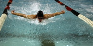 Thomas Lankiewicz ('12) swims the 100m butterfly event on Saturday at the Obermiller Pool. - Paul Kramer