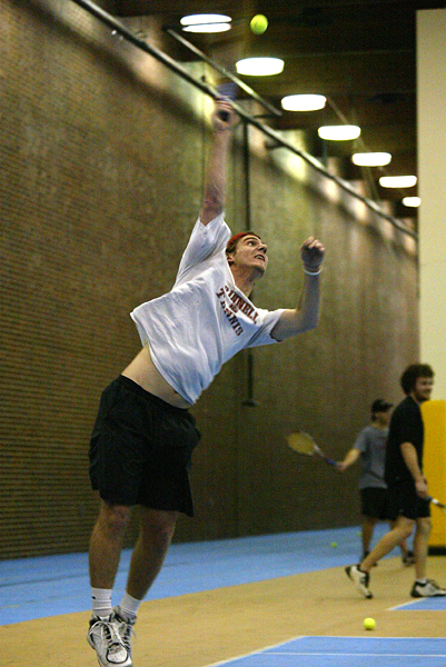 Men's Tennis Captain Dan LaFountaine '09 winds up for a powerful serve during Monday's practice in the PEC North Gym. The Pioneer tennis team is poised for another good performance at the Regional Championships. - Ben Brewer
