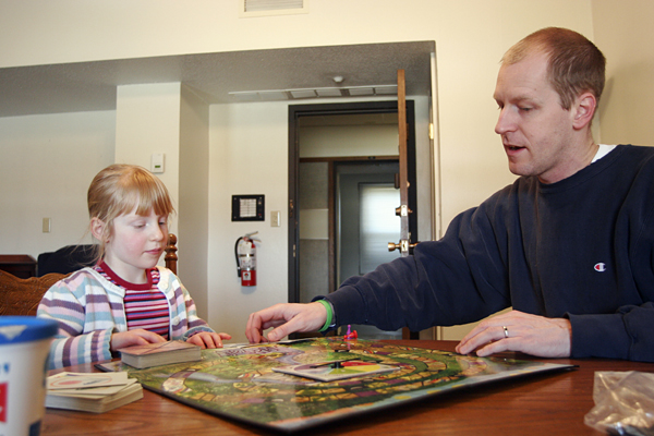Doug Cutchins '93 and his daughter Bea Geissinger-Cutchins play a board game while staying in the Langan RLC apartment last weekend. As SGA encourages the administration to develop better relations with students, Cutchins is the first administrator to temporarily reside on campus and attend campus events. - Aaron Barker