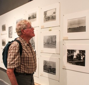 A visitor of Stewart Gallery examines the photos taken by Egbert Dunham.