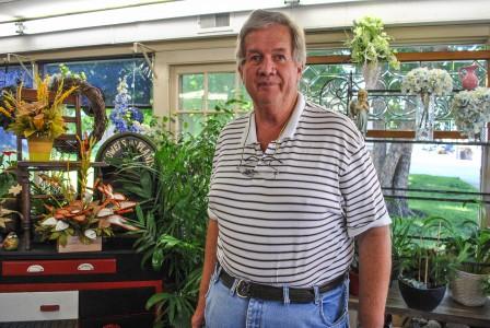 Jim White, owner of Bates Flowers, poses inside his flower store.