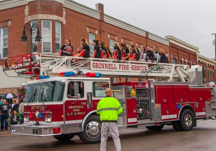 The Grinnell Fire Department rides through downtown Grinnell at the homecoming parade. Photo by Sydney Steinle.