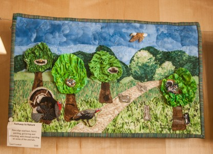 "One of the quilts on display, ""Pathway to Nature,"" featuring turkeys, squirrels and trees. Photo by Sydney Steinle."