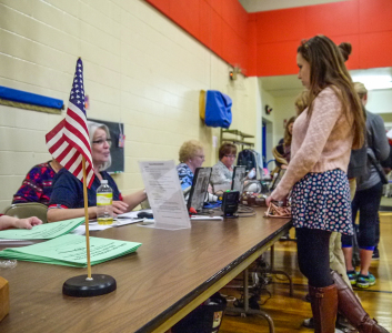 A volunteer assists a Grinnell student through the voting process in the Community Center on Election Day.  Photo by Leina'ala Voss.