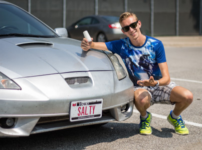"Adam ""Salty"" Dalton '16 squats next to his luxury sedan with a fitting vanity plate.   Photo by Matt Kartanata"