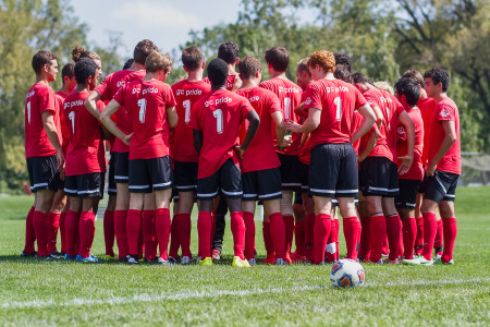 Past and present members of the Grinnell soccer team huddle last Sunday at the alumni match.  Photo by Misha Gelnarova