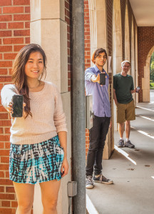 From left: Ruth Wu, Yazan Kittaneh and Alex French (all '17) show their smartphones while posing in the North Campus loggia. Photo by Rae Kuhlman