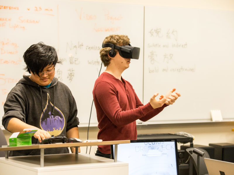 Co-founder and co-leader of Grinnell College Virtual Reality Club Richard Li '17 assists a student trying out the new virtual reality technology. Photo by Garrett Wang.